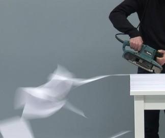 Une ponceuse et un tas de feuilles de papier