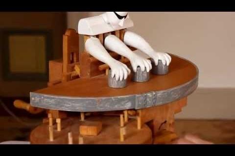 Une machine en bois qui joue au jeu des gobelets