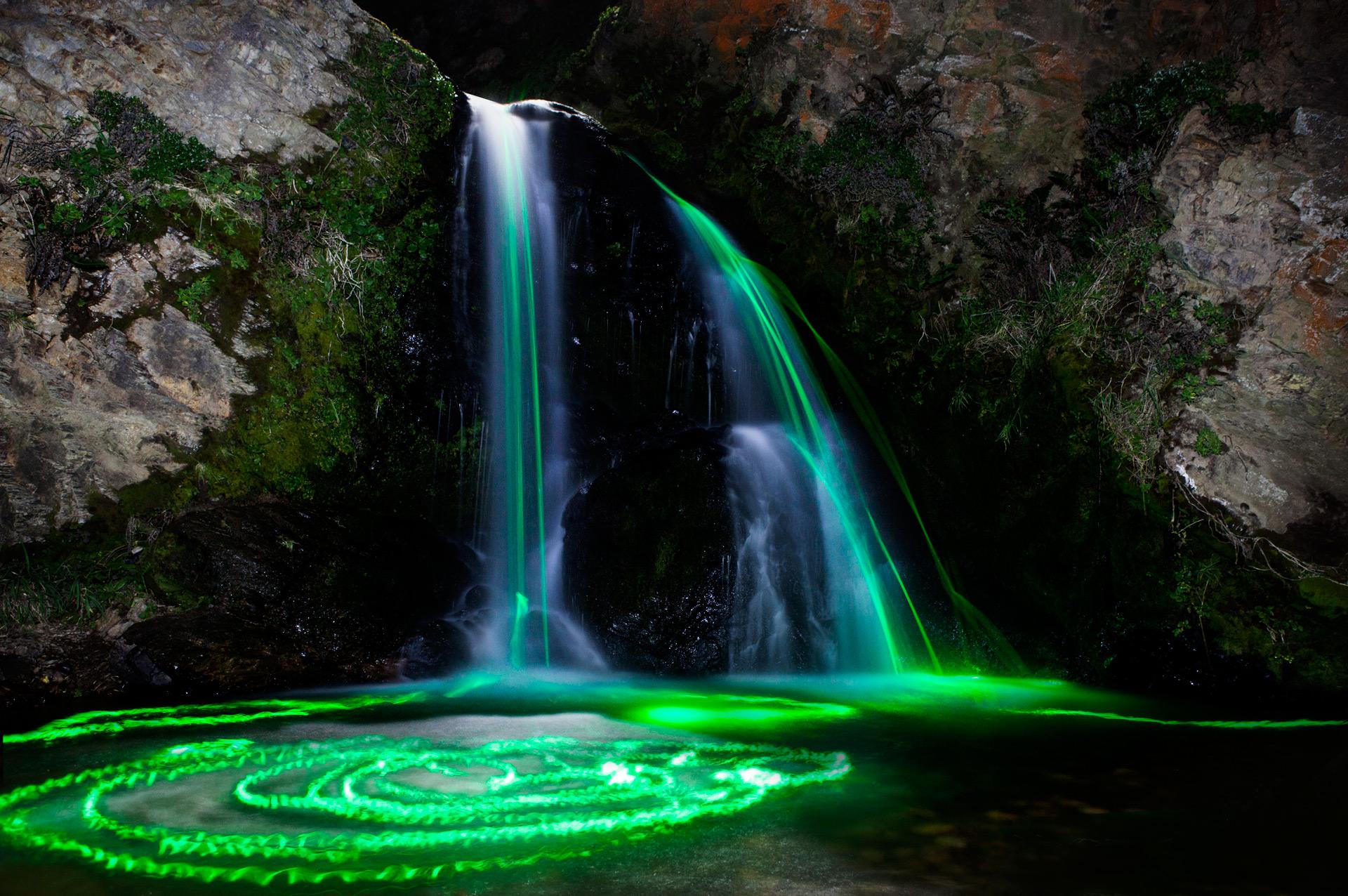 Des bâtonnets lumineux dans des cascades la nuit