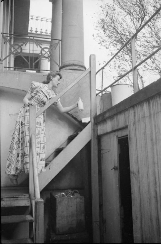 Mrs Olive Day va chercher le lait et le journal posés en haut des escaliers qui emmènent vers son sous sol. Les seaux  contiennent du sable et de l'eau et étaient fournis en cas de bombe incendiaire.