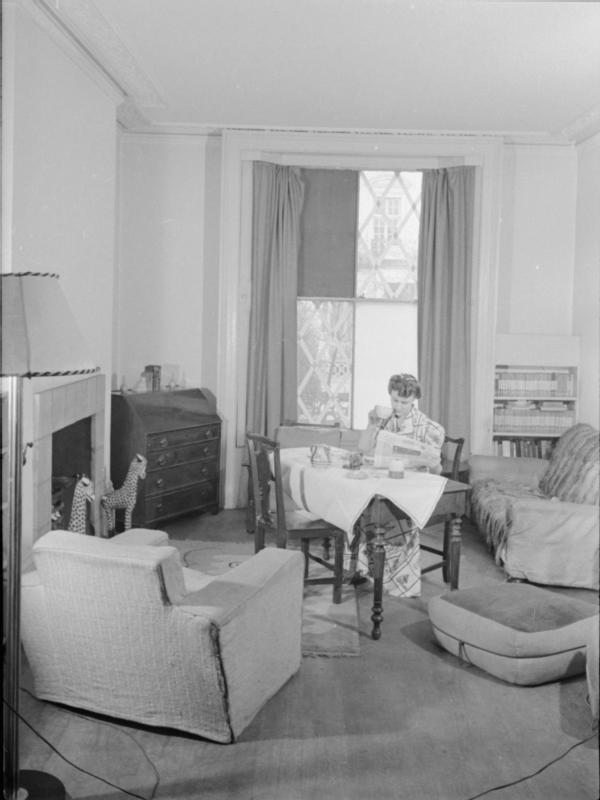 Mrs Olive Day bois son thé en lisant le journal dans son salon, certaines vitres de la fenêtre ont été cassée par une bombe, les autres sont  recouvertes de scotch pour éviter les éclats.
