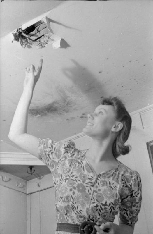 Mrs Olive Day montre un trou dans le plafond par lequel une bombe incendiaire est récemment passée.