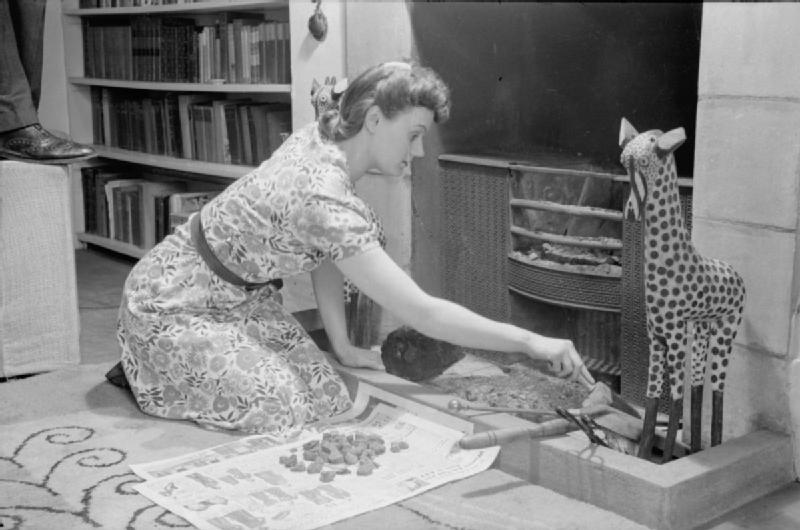 Mrs Olive Day nettoie le foyer de la cheminée, elle met de coté les charbons pour les réutiliser.