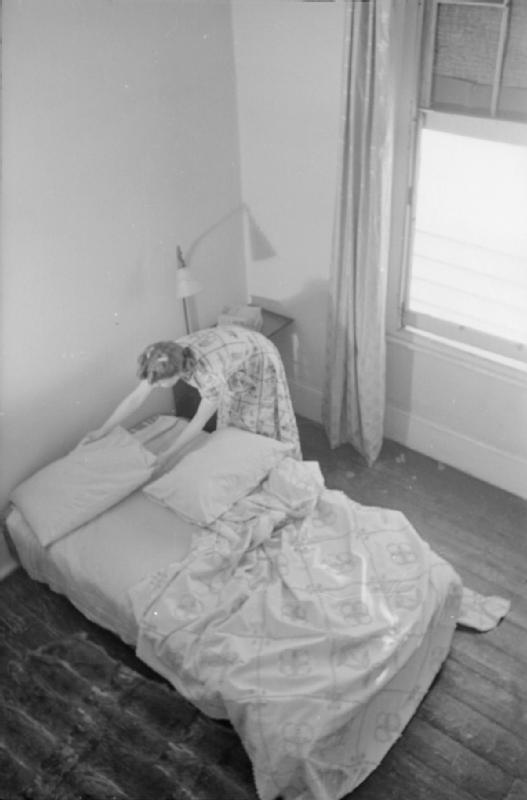 Mrs Olive Day fait son lit qu a été déplacé au rez de chaussée, l'étage étant trop dangereux.