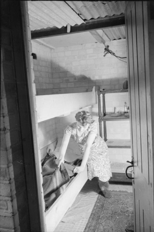 Mrs Olive Day fait le lit de camp placé dans son sous-sol dans lequel elle ira dormir en cas d'alarme de raid aérien.