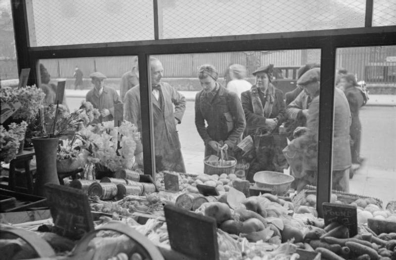 Mrs Olive Day regarde dans la vitrine d'une boutique les produits disponibles.