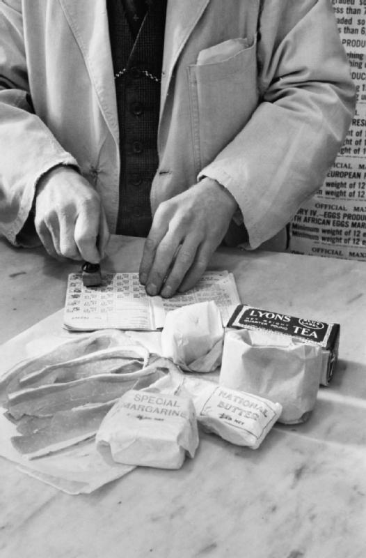 L'épicier tamponne le carnet de rationnement de Mrs Olive Day, on voit sur la photo le thé, le sucre, la margarine, le gras et le bacon qui lui sont alloués pour la semaine.