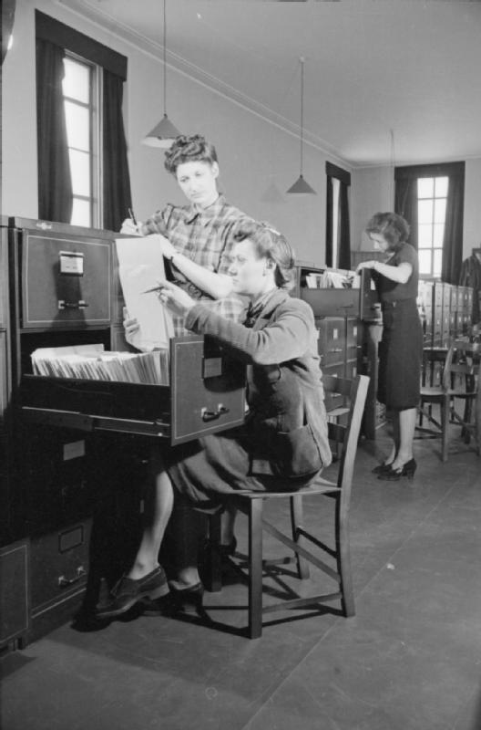 """Mrs Olive Day au travail comme secrétaire dans une """"organisation reliée à la guerre"""". Elle travaille en semaine de 10h à 18h et le samedi juqu'à 14h."""