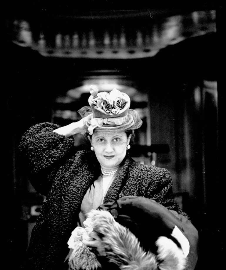 Woman adjusting flowered hat while looking in tric