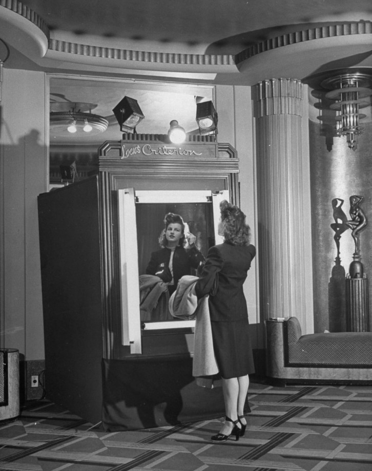 Lady fixing her hair in front of trick mirror, wit