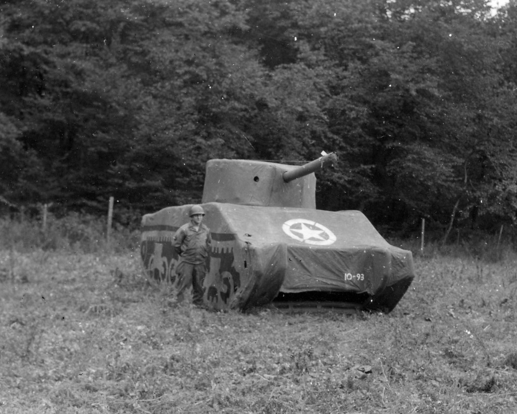 Ghost Army - A Ghost Army soldier stands next to an inflatable M4 Sherman tank.