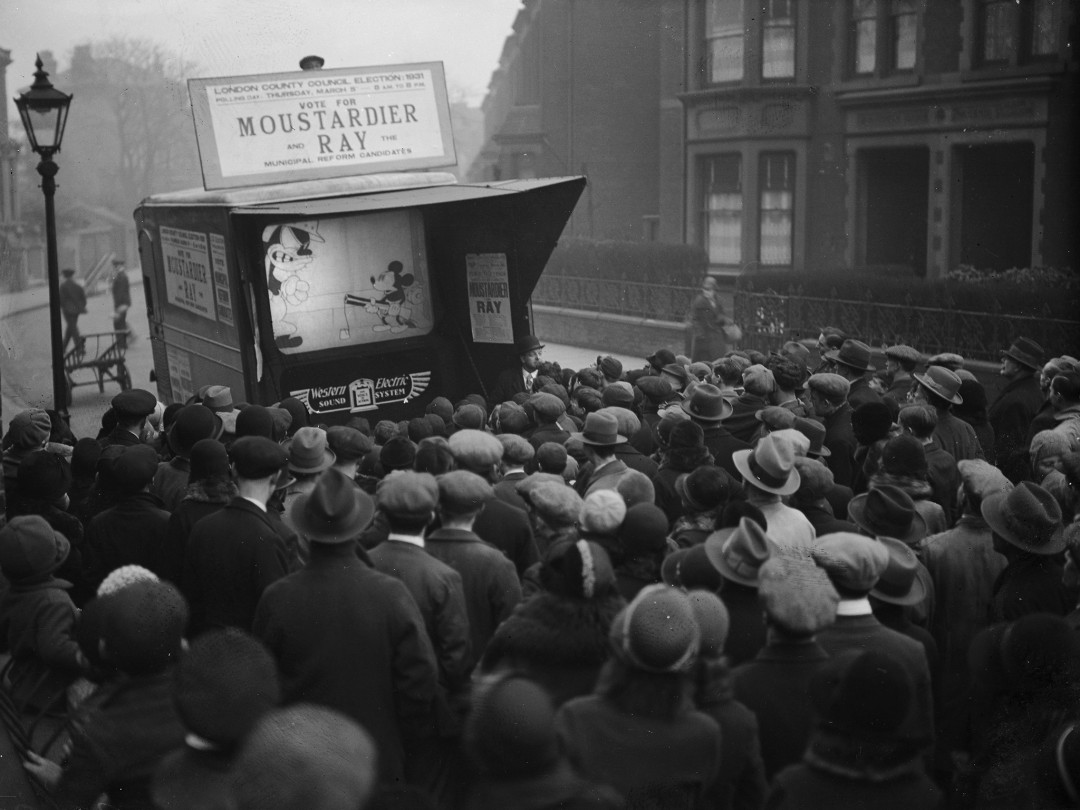 Mickey Mouse is shown on a small screen in a city street, London, 1931