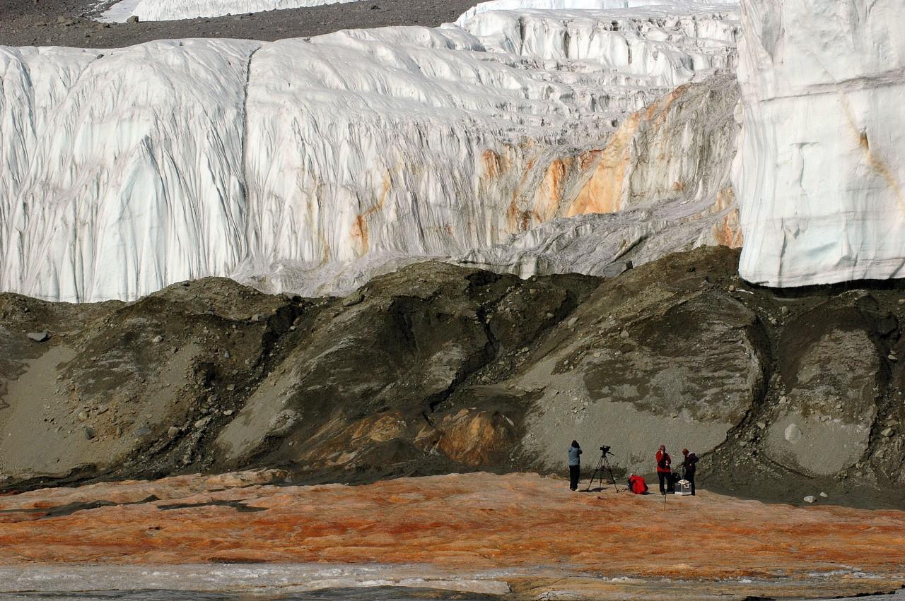 Les hydroxydes de fer, peu solubles, se déposent après que les ions ferreux, présents dans l'eau riche en sel, se sont oxydés au contact de l'oxygène atmosphérique. Ces ions proviennent de l'ancienne poche d'eau de mer de l'océan Austral qui fut piégée dans le fjord par le glacier au Miocène, il y a cinq millions d'années, lorsque le niveau de la mer était plus haut qu'aujourd'hui - Peter Rejcek