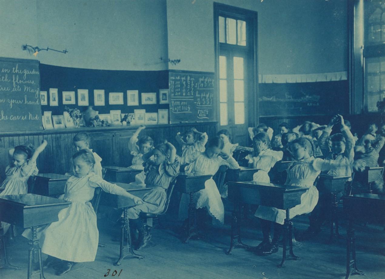 Des écoliers font des mouvements de gymnastique à leur bureau