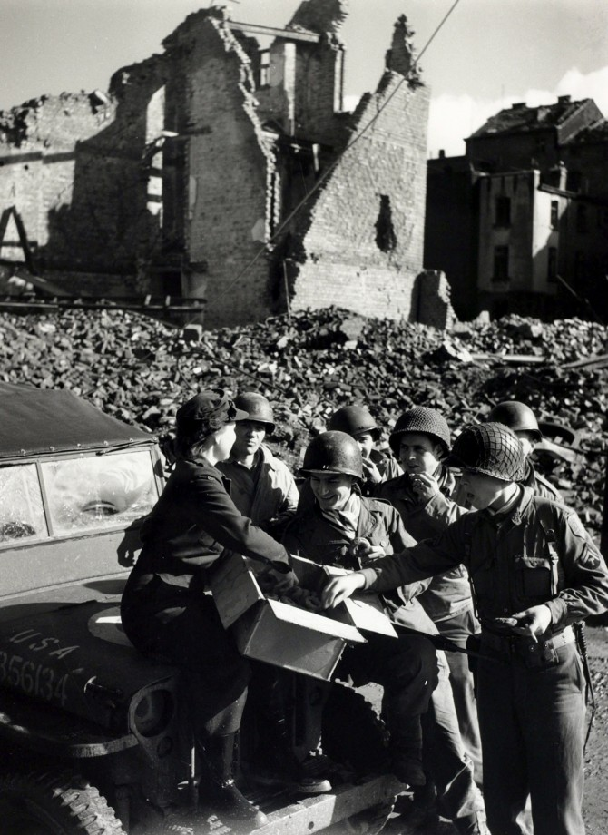 War and Conflict, World War II, pic: 19th October 1944, American soldiers receive doughnuts from a Red Cross worker in the shattered streets of Aachen, Germany (Photo by Popperfoto/Getty Images)