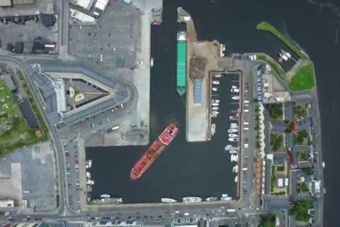 Un gros bateau qui se gare dans un petit port